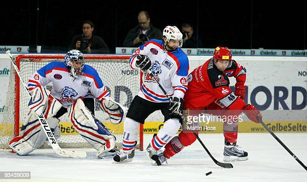 Klaus Kathan of Hannover and Dan Spang of Nuernberg battle for the puck during the DEL match between Hannover Scorpions and Thomas Sabo Ice Tigers at...
