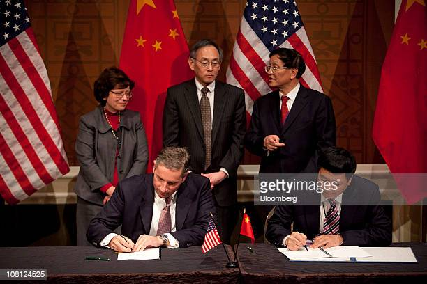 Klaus Kleinfeld president and chief executive officer of Alcoa Inc left signs an agreement with Lu Qizhou president of China Power Investment Corp...