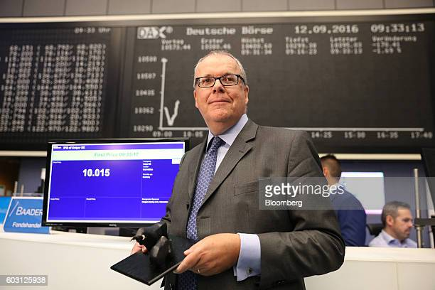 Klaus Schaefer chief executive officer of Uniper SE poses for a photograph beside a screen showing the opening trading price as Uniper makes its...