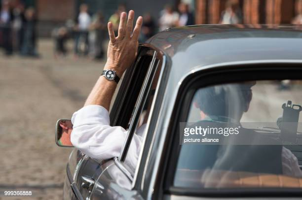 Klaus Ziegner waves his hand to the fans out of his Peugeot 404 Super Luxe built in 1964 at the start of the HamburgBerlin Vintage Car Rallye in...