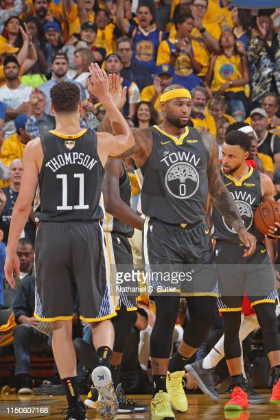 Klay Thompson and DeMarcus Cousins of the Golden State Warriors high five against the Toronto Raptors during Game Six of the 2019 NBA Finals on June...