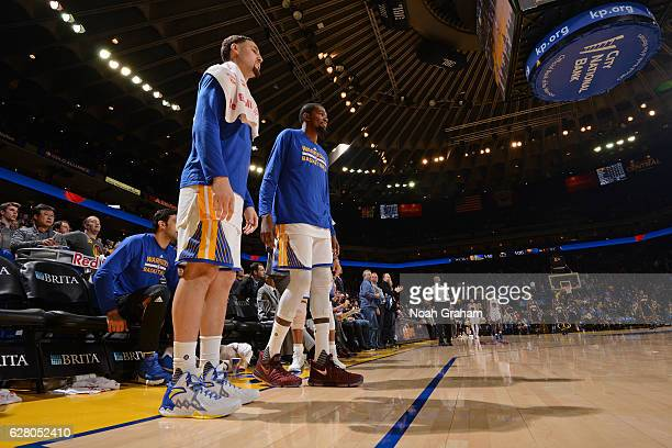 Klay Thompson and Kevin Durant of the Golden State Warriors look on from the bench during the game against the Indiana Pacers on December 5 2016 at...