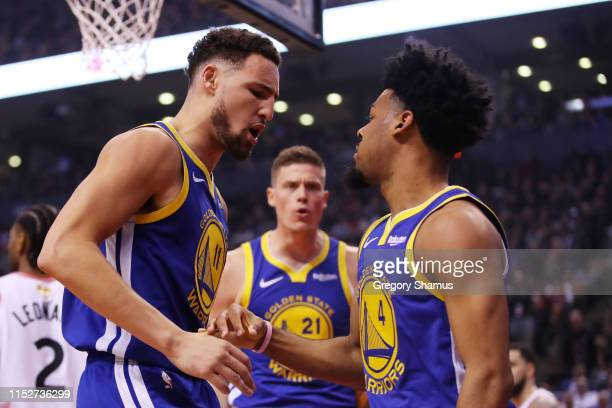 Klay Thompson and Quinn Cook of the Golden State Warriors celebrate the play against the Toronto Raptors in the second quarter during Game One of the...