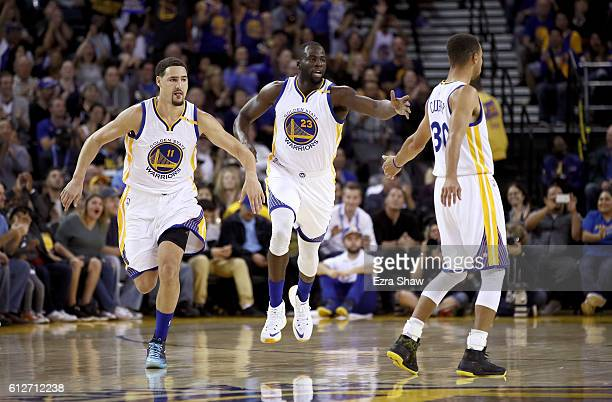 Klay Thompson and Stephen Curry congratulate Draymond Green of the Golden State Warriors after he made a basket against the Los Angeles Clippers...