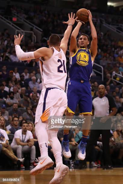 Klay Thompson of the Golden State Warriors attempts a shot over Alex Len of the Phoenix Suns during the first half of the NBA game at Talking Stick...