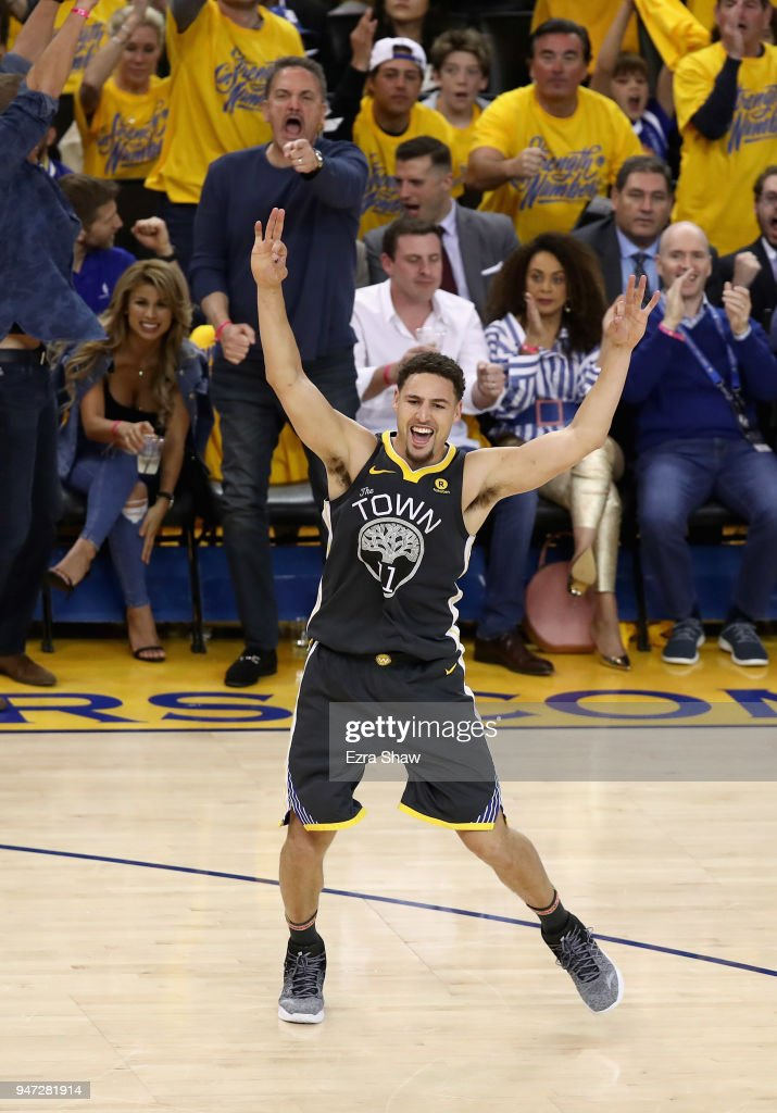 Klay Thompson #11 of the Golden State Warriors celebrates after Quinn Cook #4 made a three-point basket against the San Antonio Spurs during Game 2 of Round 1 of the 2018 NBA Playoffs at ORACLE Arena on April 16, 2018 in Oakland, California.