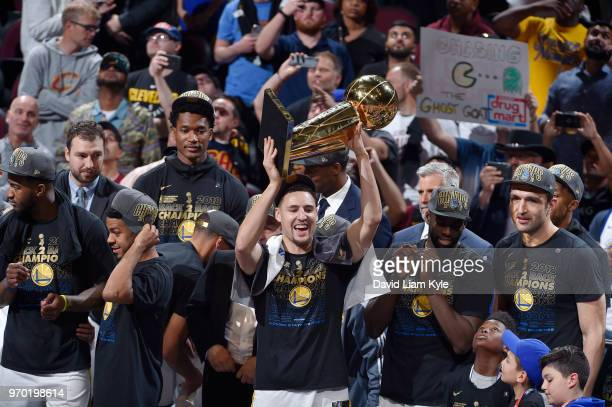 Klay Thompson of the Golden State Warriors celebrates after the game against the Cleveland Cavaliers while holding the Larry O'Brien NBA Championship...