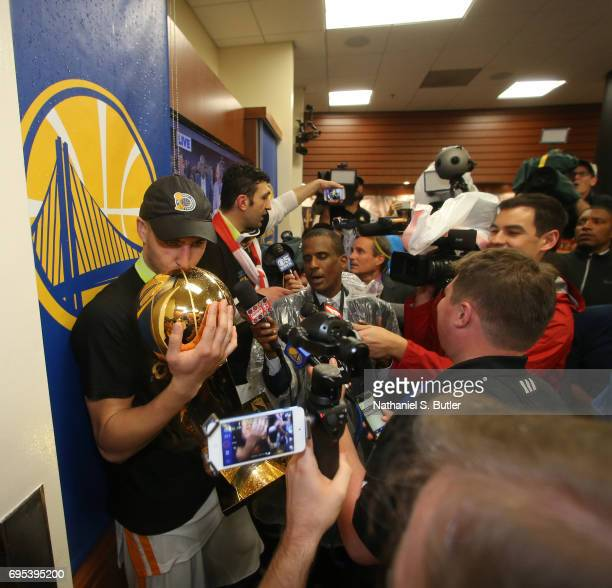 Klay Thompson of the Golden State Warriors celebrates and kisses the Larry O'Brien Trophy in the locker room after winning the NBA Championsip in...