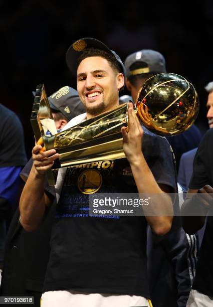 Klay Thompson of the Golden State Warriors celebrates with the Larry O'Brien Trophy after defeating the Cleveland Cavaliers during Game Four of the...