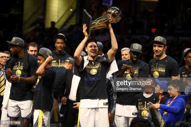 Klay Thompson of the Golden State Warriors celebrates with the Larry O'Brien Trophy after defeating the Cleveland Cavaliers in Game Four of the 2018...