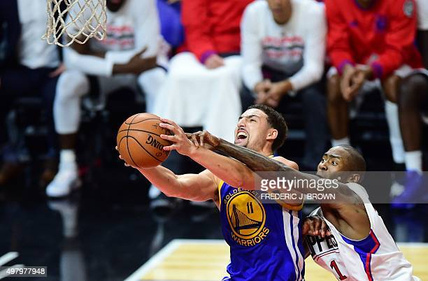 Klay Thompson of the Golden State Warriors goes to the basket under pressure from Jamaal Crawford of the Los Angeles Clippers during their NBA game...