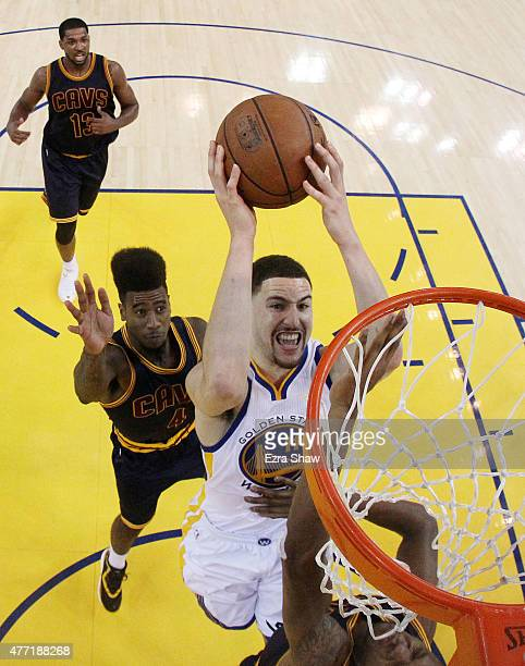 Klay Thompson of the Golden State Warriors goes up against James Jones and Iman Shumpert of the Cleveland Cavaliers in the second half during Game...
