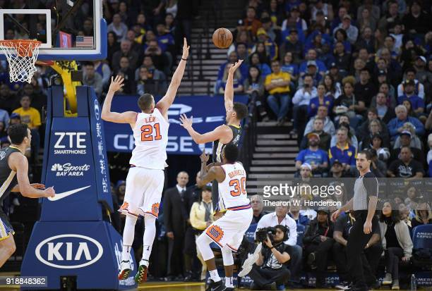 Klay Thompson of the Golden State Warriors goes up to shoot over Alex Len and Troy Daniels of the Phoenix Suns during an NBA basketball game at...