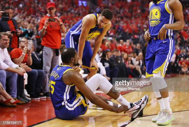 Klay Thompson of the Golden State Warriors helps Kevin Durant to his feet in the first half against the Toronto Raptors during Game Five of the 2019...