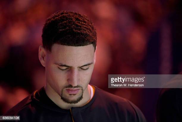 Klay Thompson of the Golden State Warriors holds his head down with eyes closed during the singing of the National Anthem prior to the start of an...