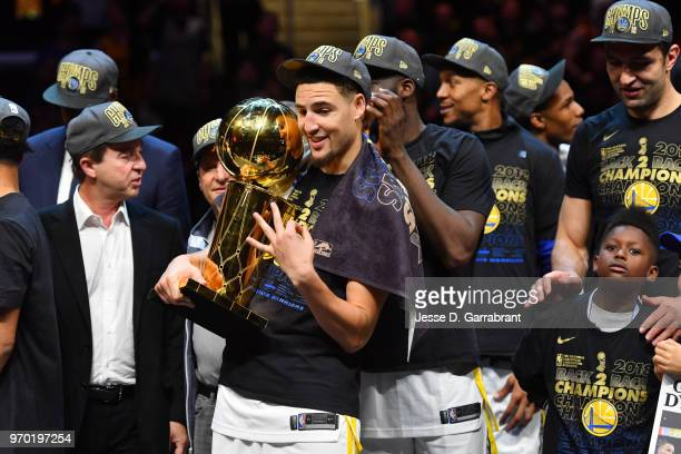 Klay Thompson of the Golden State Warriors holds the Larry O'Brien Championship trophy after defeating the Cleveland Cavaliers in Game Four of the...