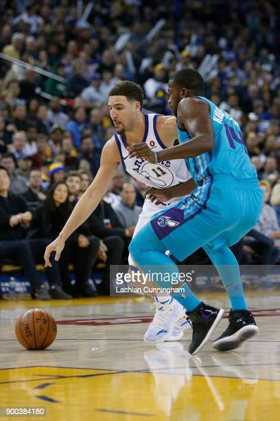 Klay Thompson of the Golden State Warriors is guardedly by Michael KiddGilchrist of the Charlotte Hornets at ORACLE Arena on December 29 2017 in...