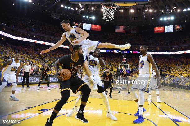 Klay Thompson of the Golden State Warriors is upended between Draymond Green and Tristan Thompson of the Cleveland Cavaliers in Game 5 of the 2017...