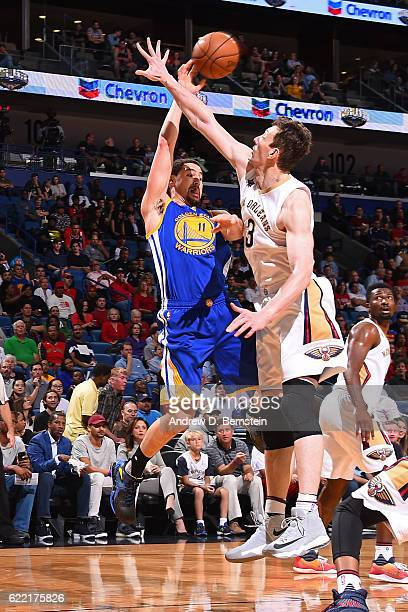Klay Thompson of the Golden State Warriors passes the ball against Omer Asik of the New Orleans Pelicans during a game at Smoothie King Center on...