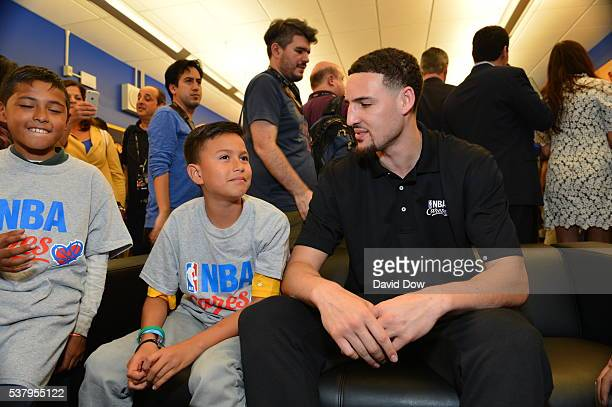 Klay Thompson of the Golden State Warriors plays a video game with children at the 2016 NBA Finals Cares Legacy project as part of the 2016 NBA...