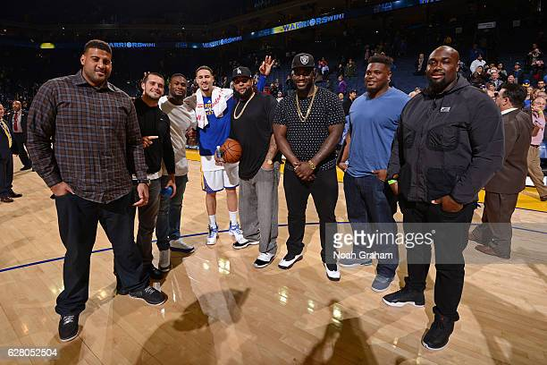 Klay Thompson of the Golden State Warriors poses for a photo with Oakland Raiders Latavious Murray Derek Carr Gabe Jackson Austin Howard and Donald...