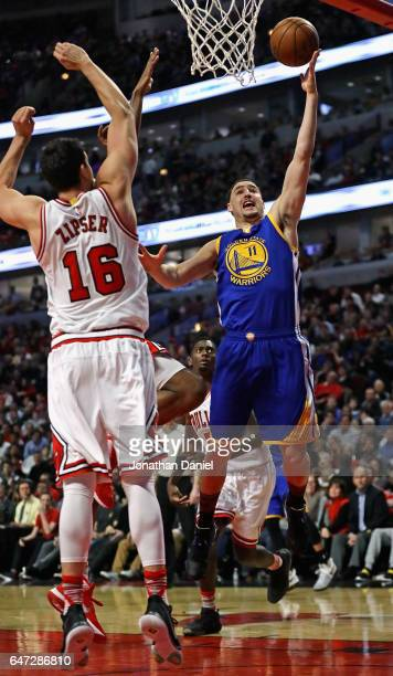 Klay Thompson of the Golden State Warriors puts up a shot against Paul Zipser of the Chicago Bulls at the United Center on March 2 2017 in Chicago...