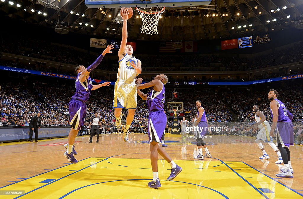 Klay Thompson #11 of the Golden State Warriors shoots a layup against Ray McCallum #3 and Travis Outlaw #25 of the Sacramento Kings on April 4, 2014 at Oracle Arena in Oakland, California.