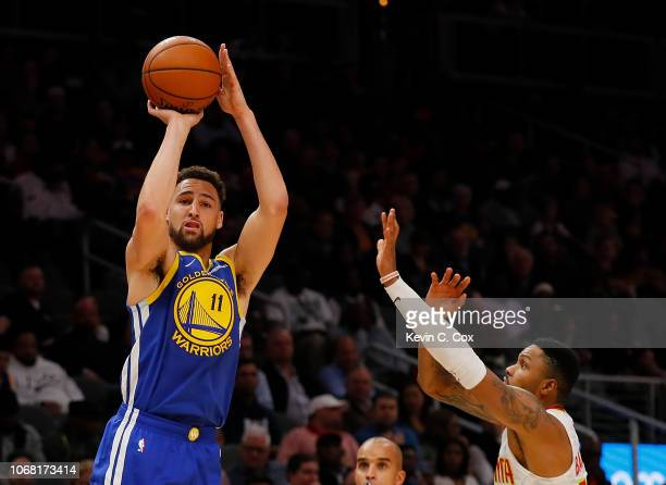 Klay Thompson of the Golden State Warriors shoots a threepoint basket against Kent Bazemore of the Atlanta Hawks at State Farm Arena on December 3...