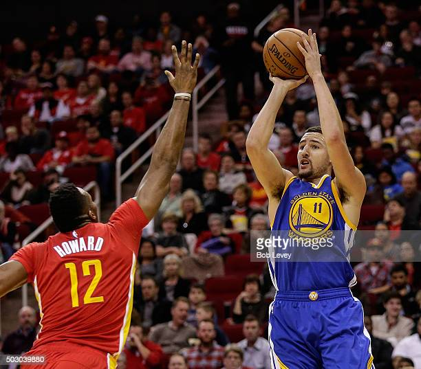 Klay Thompson of the Golden State Warriors shoots ocer the outstretched arm of Dwight Howard of the Houston Rockets in the second half at Toyota...
