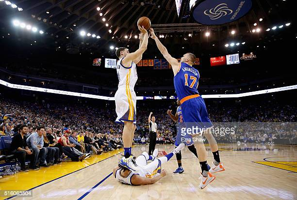 Klay Thompson of the Golden State Warriors shoots over Lou Amundson of the New York Knicks at ORACLE Arena on March 16 2016 in Oakland California...