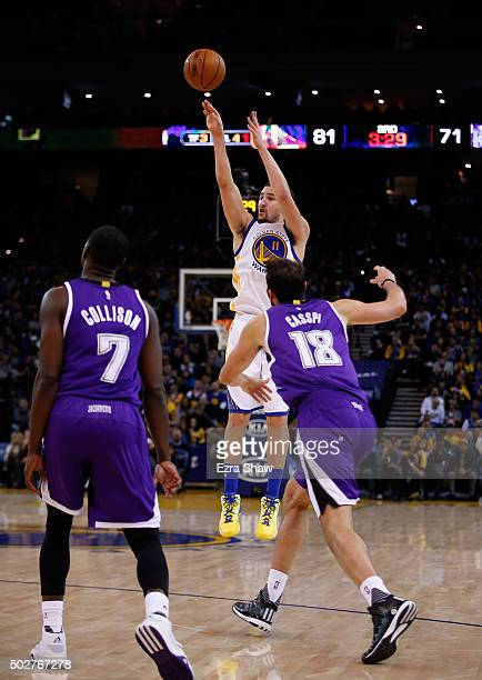 Klay Thompson of the Golden State Warriors shoots over Omri Casspi of the Sacramento Kings at ORACLE Arena on December 28 2015 in Oakland California...
