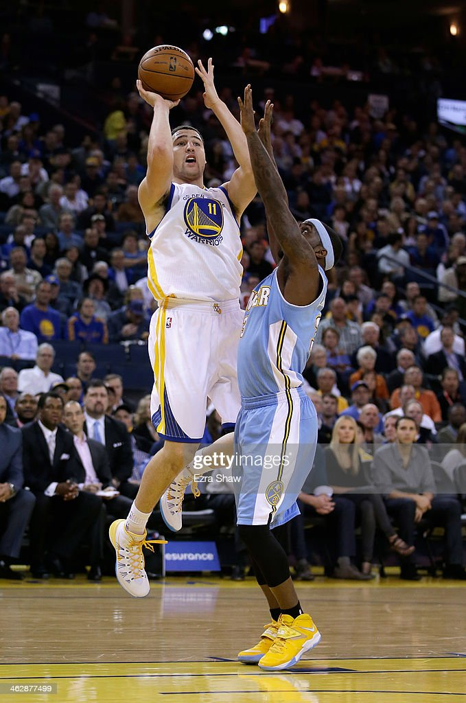 Klay Thompson #11 of the Golden State Warriors shoots over Ty Lawson #3 of the Denver Nuggets at ORACLE Arena on January 15, 2014 in Oakland, California.