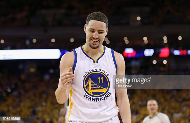 Klay Thompson of the Golden State Warriors smiles as he goes to help Leandro Barbosa off the ground during their game against the Portland Trail...