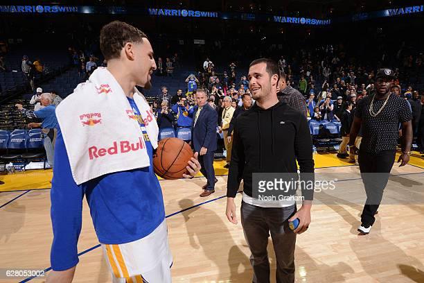 Klay Thompson of the Golden State Warriors talks to Oakland Raider Derek Carr after the game against the Indiana Pacers on December 5 2016 at ORACLE...