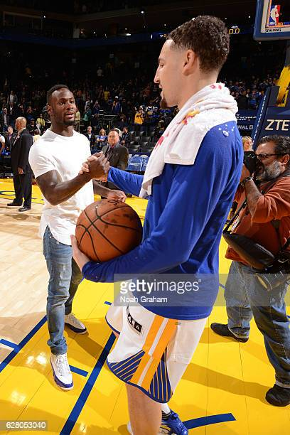 Klay Thompson of the Golden State Warriors talks to Oakland Raider Latavious Murray after the game against the Indiana Pacers on December 5 2016 at...