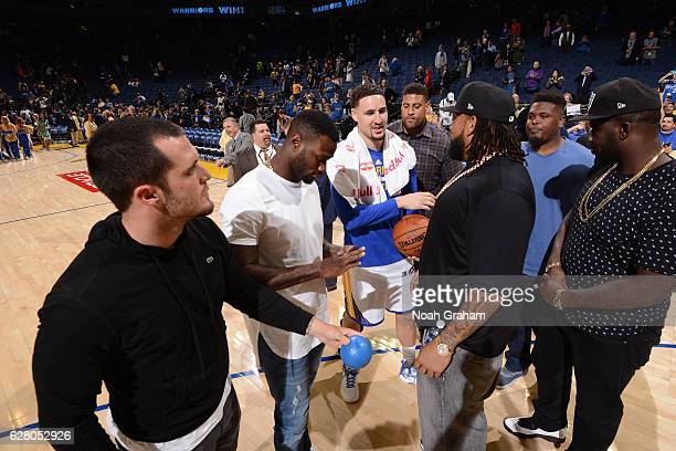Klay Thompson of the Golden State Warriors talks to Oakland Raiders Latavious Murray Derek Carr and Donald Penn after the game against the Indiana...