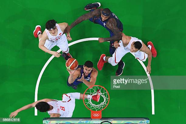 Klay Thompson of United States goes to the basket against Yanyuhang Ding and Jianlian Yi of China in the Men's Preliminary Round Group A match on Day...