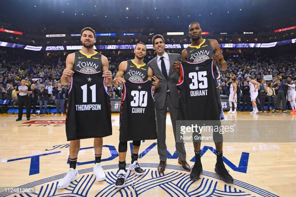 Klay Thompson Stephen Curry and Kevin Durant of the Golden State Warriors pose for a photo with Bob Meyers holding up their Charlotte AllStar...