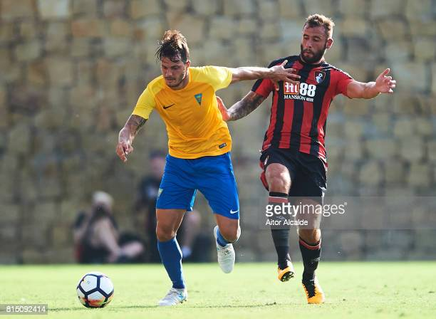 Kleber Laube of Estoril Praia competes for the ball with Steve Cook of AFC Bournemouth during a Pre Season Friendly match between AFC Bournemouth and...