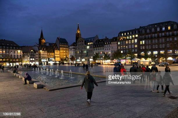 kleber square with water fountain and pedestrians at night. - emreturanphoto stock pictures, royalty-free photos & images