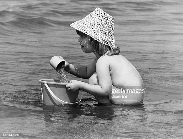 Kleines Mädchen mit Sonnenhut spielt im Wasser der Havel in Berlin 1977