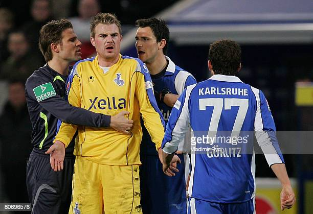 Klemen Lavric of Duisburg is holden by referee Felix Brych as he discusses with Andreas Goerlitz of Karlsruhe during the Bundesliga match between MSV...
