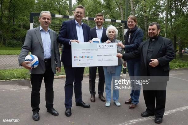Klemes Buscher, DFB President Reinhard Grindel, DFB Ambassador Thomas Hizlsperger, Elizabeth Levina and Kristof pose with check for 17,000 Euro in...