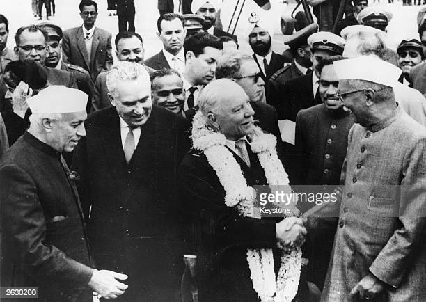Klimenti Efremovich Voroshilov Soviet President garlanded and shaking hands with Indian President Rajendra Prasad on his arrival at New Delhi airport...