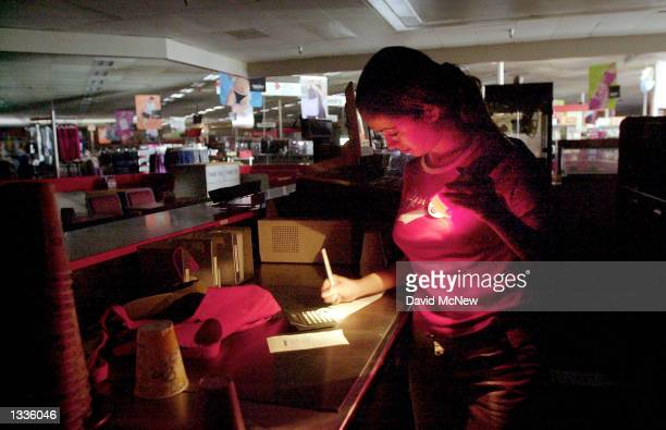 Mart store employee Maggie Brabo does paperwork by flashlight March 20 2001 when a rolling blackout hits Santa Ana CA Blackouts affecting southern...