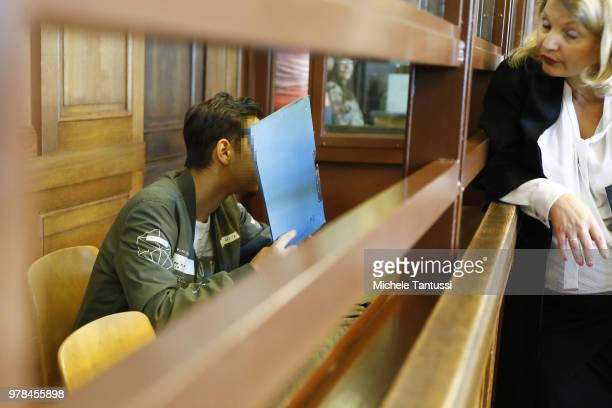 A young defendant hides his face behind a folder as he waits for the opening of his trial at the district court in Berlin where he is charged with...