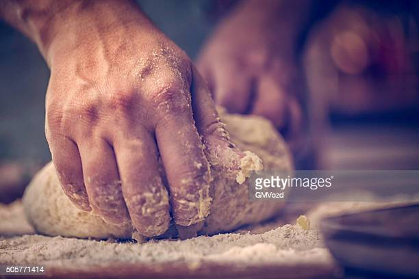 kneading dough with hands on the table - savoury food stock photos and pictures