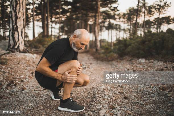 knee injury on running outdoors in forest. senior man holding knee by hands and suffering with pain. sprain ligament or meniscus problem. - old man feet stock pictures, royalty-free photos & images