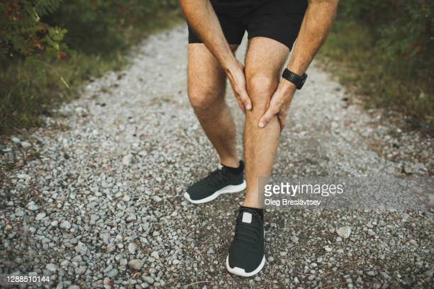 knee injury on running outdoors. man holding knee by hands close-up and suffering with pain. sprain ligament or meniscus problem. - injured stock pictures, royalty-free photos & images