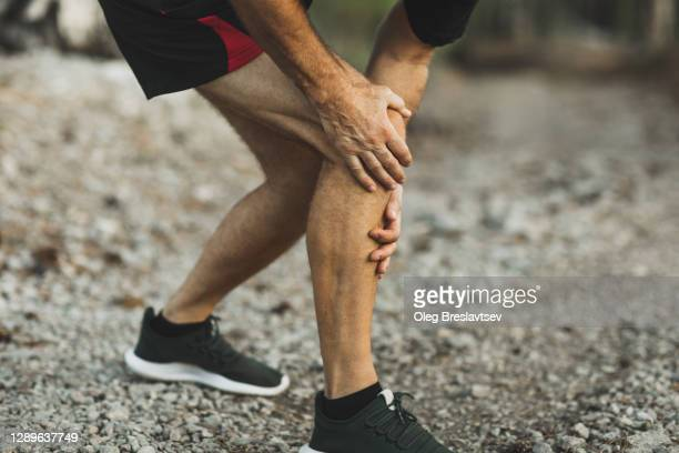 knee injury on running outdoors. man holding knee by hands close-up and suffering with pain. sprain ligament or meniscus problem. - old man feet stock pictures, royalty-free photos & images